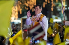 Thai King Maha Vajiralongkorn greets supporters as he walks to participate in a candle lighting ceremony to mark the…