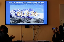 Nepalese government officers watch a live telecast of a joint announcement on the height of Mount Everest, in Kathmandu, Nepal, Dec. 8, 2020.