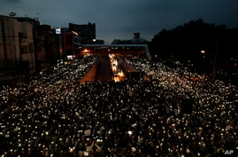 Pro-democracy activists wave mobile phones with lights during a demonstration at Kaset intersection, suburbs of Bangkok,…