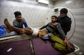 Kashmiris carry a boy who was injured in a grenade blast for treatment at a hospital in Srinagar, Indian controlled Kashmir,…