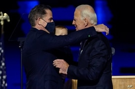 FILE - President-elect Joe Biden, right, embraces his son Hunter Biden, left, in Wilmington, Del.