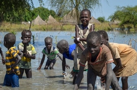Children wash themselves in muddy floodwaters in the village of Wang Chot, Old Fangak county, Jonglei state, South Sudan…