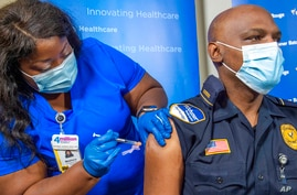Lt. Ollie Martin, right, with Ochsner Security, is inoculated with the Pfizer-BioNTech COVID-19 vaccine by nurse Meshoca…