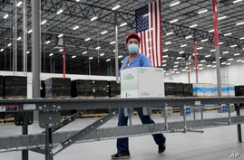 Boxes containing the Moderna COVID-19 vaccine are prepared to be shipped at the McKesson distribution center in Olive Branch,…