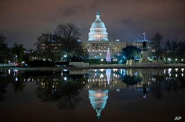 The U.S. Capitol is seen at night after negotiators sealed a deal for COVID relief, Sunday, Dec. 20, 2020, in Washington. Top…