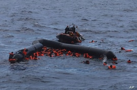 FILE - Refugees and migrants are rescued by members of the Spanish NGO Proactiva Open Arms, after leaving Libya trying to reach European soil aboard an overcrowded rubber boat in the Mediterranean sea, Nov. 11, 2020.