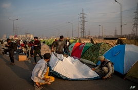 Volunteers put up tents for protesting farmers in the middle of a major highway which is blocked in a protest against new farm laws at the Delhi-Uttar Pradesh state border, India, Dec. 25, 2020.