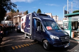 A refrigerated truck is escorted by Italian Police as it arrives at the Spallanzani hospital to deliver the first doses of vaccine for the COVID-19 in Rome, Dec. 26, 2020.