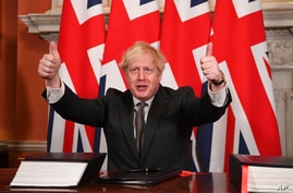 Britain's Prime Minister Boris Johnson gives a thumbs up gesture after signing the EU-UK Trade and Cooperation Agreement at 10…