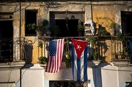 FILE - In this Dec. 19, 2014 file photo, a U.S. and Cuban flag hang from a balcony in Old Havana, Cuba. As the two countries to…