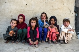FILE - Children sit in front of a house at Deh Qubad village in Maiwand district of Kandahar province, Afghanistan, Sept. 27, 2020.