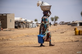 FILE - A woman walks at the Goudebo refugee camp for Malian refugees in Dori, Burkina Faso, Feb. 3, 2020.