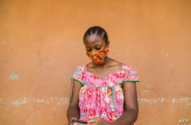 FILE - A woman checks her phone in Yaounde, Cameroon, April 23, 2020. An International Crisis Group report has found hate speech spread through social media to be a major contributor to ethnic and political tensions in the country.