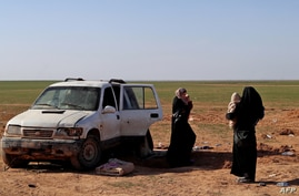 FILE - Two women, wives of an Islamic State fighter who has been identified as a German national, wait to be screened and registered by Syrian Democratic Forces, in the countryside of the eastern Syrian Deir Ezzor province, Jan. 31, 2019.
