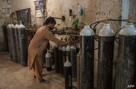 A worker fills oxygen tanks for use in hospitals in Peshawar, Pakistan, Dec. 7, 2020.