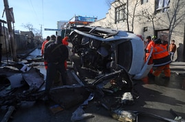 Afghan security personnel and municipality workers remove a damaged vehicle after a roadside bomb attack in Kabul, Dec. 22, 2020.