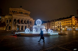 A man passes by the illuminated fountain in front of the Old Opera in Frankfurt, Germany, Dec. 10, 2020.