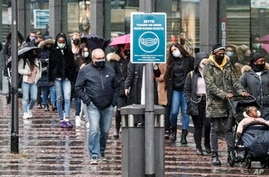 People queue in front of a shop in the city center of Essen, Germany, Dec. 14, 2020.