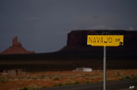 FILE - A sign for Navajo Drive is seen against cloud-darkened Oljato-Monument Valley, Utah, on the Navajo Reservation, April 30, 2020. Across the nation, Native American tribes are working to protect their oldest members from COVID.