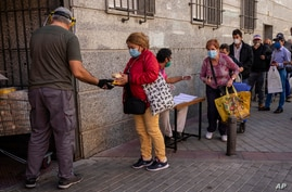 People collect food donated by volunteers and members of the Catholic Servants of Jesus congregation in Madrid, Spain, Oct. 8, 2020.