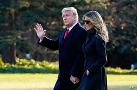 President Donald Trump and first lady Melania Trump walk to board Marine One on the South Lawn of the White House, Dec. 23, 2020, in Washington.