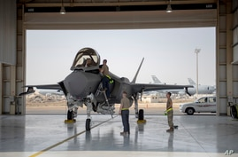 FILE - In this Aug. 5, 2019, photo released by the U.S. Air Force, an F-35 fighter jet pilot and crew prepare for a mission at Al-Dhafra Air Base in the United Arab Emirates.