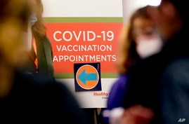 FILE - A COVID-19 vaccination appointments sign points the way at Edward Hospital in Naperville, Illinois, Dec. 17, 2020.