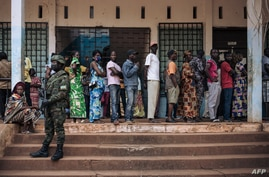 A Rwandan soldier looks on as as voters queue to vote at the Barthélemy Boganda high school polling station in the 1st district…