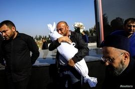 Timur Xaligov carries his 10-month-old daughter, who was killed with five other relatives, including her mother, when a rocket hit their home during the fighting over the breakaway region of Nagorno-Karabakh, in Ganja, Azerbaijan, Oct. 17, 2020.