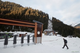 A man walks next to a closed chairlift at Les Portes du Soleil ski resort during the global outbreak of the coronavirus disease (COVID-19), in Chatel, France, Dec. 19, 2020.