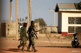 Military men walk inside the Government Science school in Kankara, in northwestern Katsina state, Nigeria, Dec. 13, 2020.