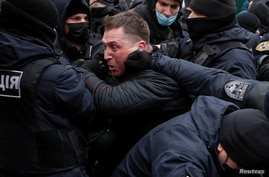 Law enforcement officers restrain a demonstrator during a rally of entrepreneurs and representatives of small businesses amid the COVID-19 outbreak in Kyiv, Ukraine.
