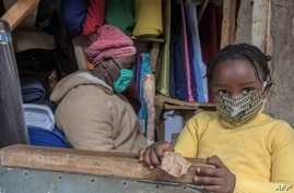 A woman who trades in fabrics, and her child, wears face masks as preventive measure against the COVID-19 coronavirus, in her…