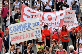 People hold placards and banners during a demonstration called by far-right and COVID-19 deniers to protest against…