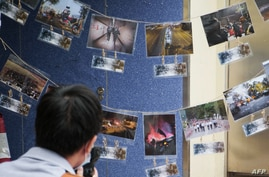 This photograph taken on November 14, 2020 shows a photographer in front of pictures depicting the 2019 campus siege at the…