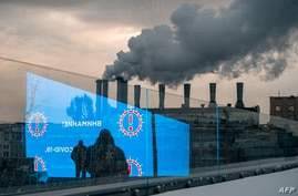 Pedestrians and an electronic screen displaying epidemic prevention advices are reflecting in a glass wall in Moscow on…