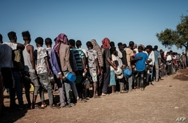 Ethiopian refugees who fled the Ethiopia's Tigray conflict wait in a line for the food distribution by Muslim Aid at the Um…