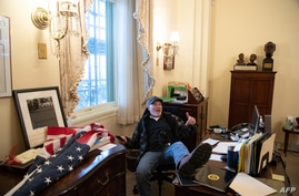 Richard Barnett, a supporter of US President Donald Trump sits inside the office of US Speaker of the House Nancy Pelosi as he…