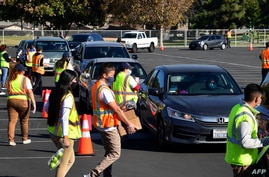 (FILES) In this file photo taken on December 04, 2020, food is loaded as drivers in their vehicles wait in line on arrival at a…