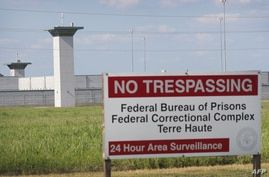 (FILES) In this file photo a sign warns away trespassers at the Federal Correctional Complex Terre Haute on July 25, 2019 in…