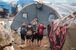 Children look on as they stand next to a tent at a flooded camp for Syrians displaced by conflict near the village of Kafr Uruq…