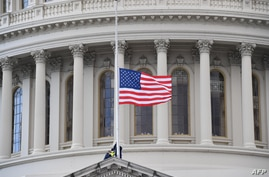 A US flag is raised after the inauguration of Joe Biden as the 46th US President on January 20, 2021, at the US Capitol in…
