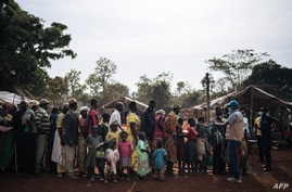 A United Nations High Commissioner for Refugees (UNHCR) worker welcomes Central African refugees at the entrance of a refugee…