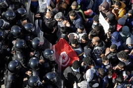 Police block protesters from not accessing parliament , on January 26, 2021 in Tunis. Tunisia braced for further protests after…
