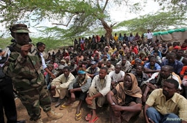 FILE - Members of the militant group al Shabab listen to a Somalia government soldier after their surrender to the authorities in Mogadishu, Sept. 24, 2012.