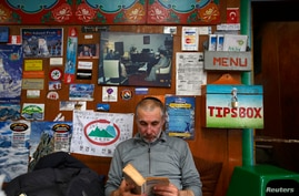 FILE - American climber Alex Goldfarb, who had to cancel his planned climb of Mount Lhotse, reads a book in Solukhumbu District May 5, 2014.