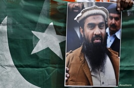FILE - A supporter of Shiv Sena, a Hindu hardline group, holds Pakistan's national flag and a portrait of Zaki-ur-Rehman Lakhvi during a protest against Lakhvi's release, in New Delhi, April 11, 2015.