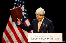 U.S. Secretary of State John Kerry reacts as he delivers a statement on the Iran talks deal at the Vienna International Center…