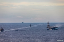 FILE - Japan Maritime Self-Defense Force training ships JS Kashima and JS Shimayuki conduct a passing exercise (PASSEX) with Nimitz-class nuclear-powered aircraft carrier USS Ronald Reagan in the South China Sea, July 7, 2020.