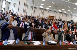 Somali parliament members raise up their hands to approve the appointment of Somalia's new prime minister Mohamed Hussein Roble…